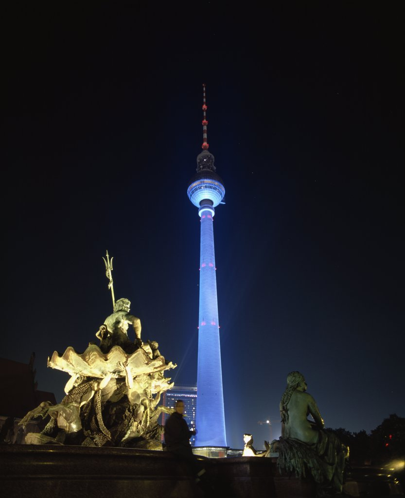 Television tower and statue of Neptune illuminated at night, Berlin, Germany : Stock Photo