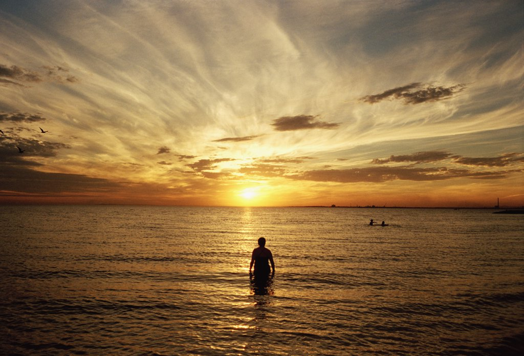 Man standing in sea at sunset : Stock Photo