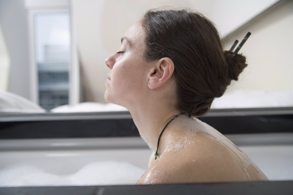 Stock Photo: 1570R-102591 Profile of woman with brown hair in bathtub
