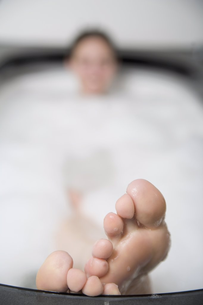 Woman lying in bathtub with feet resting on the edge : Stock Photo