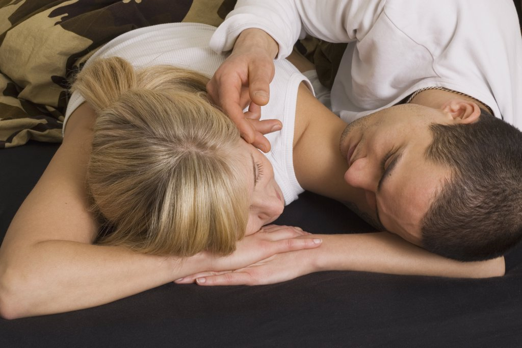 Young couple lying down on bed : Stock Photo