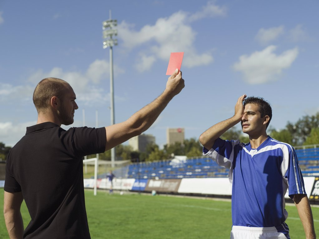 A soccer player being given a red card : Stock Photo
