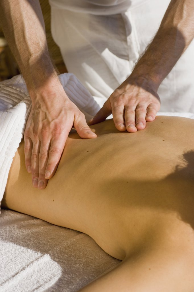 Stock Photo: 1570R-103315 Young woman lying on front receiving back massage