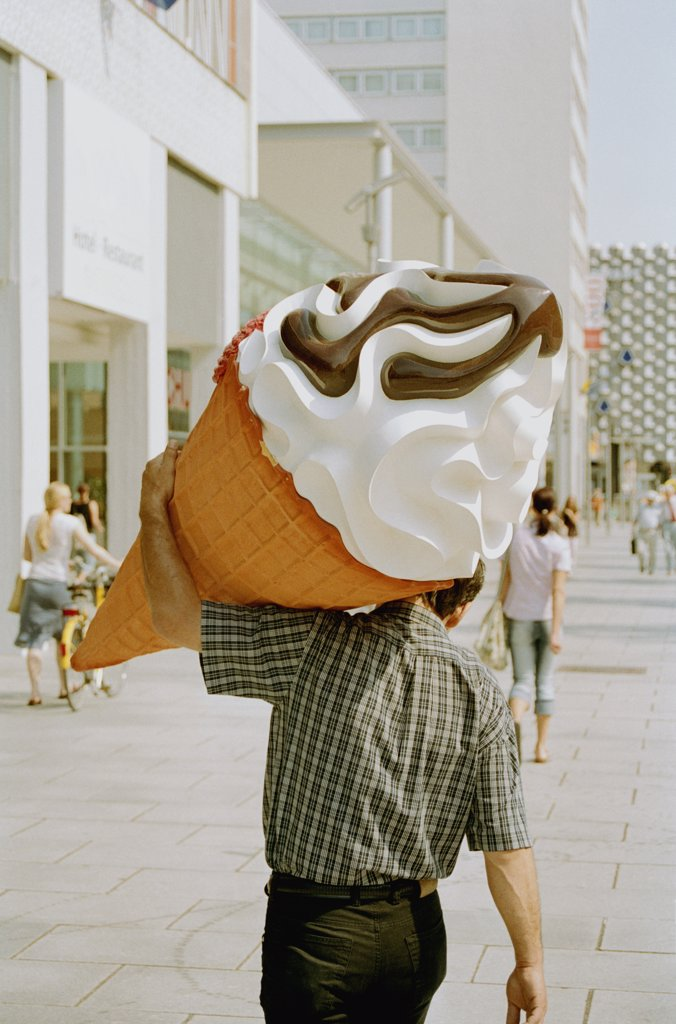 Man carrying large plastic ice cream : Stock Photo