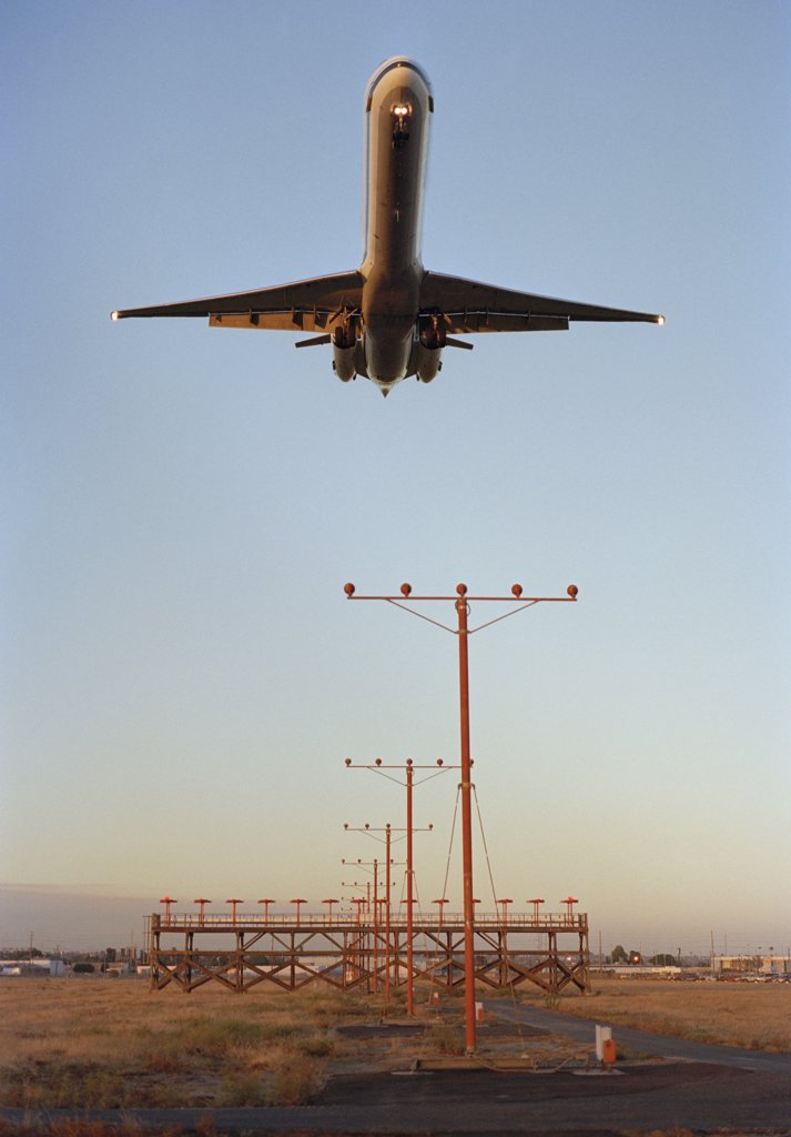 Stock Photo: 1570R-103855 Airplane landing at dusk