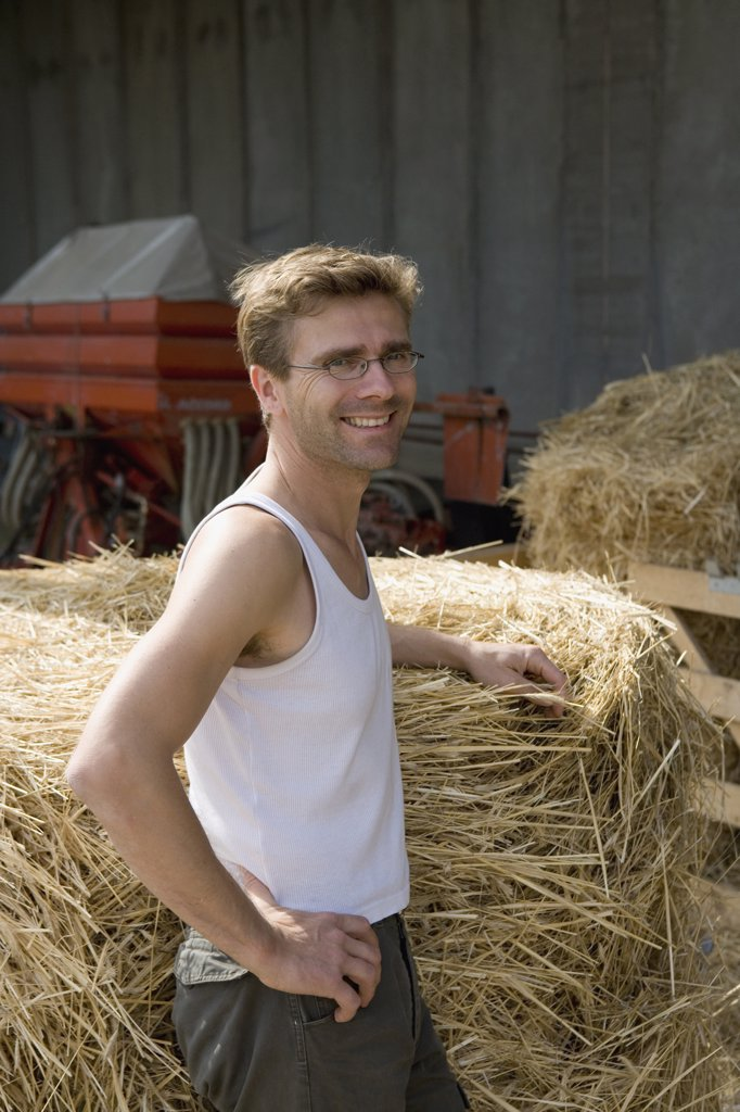 Stock Photo: 1570R-113786 Farm worker resting next to bale of hay and smiling