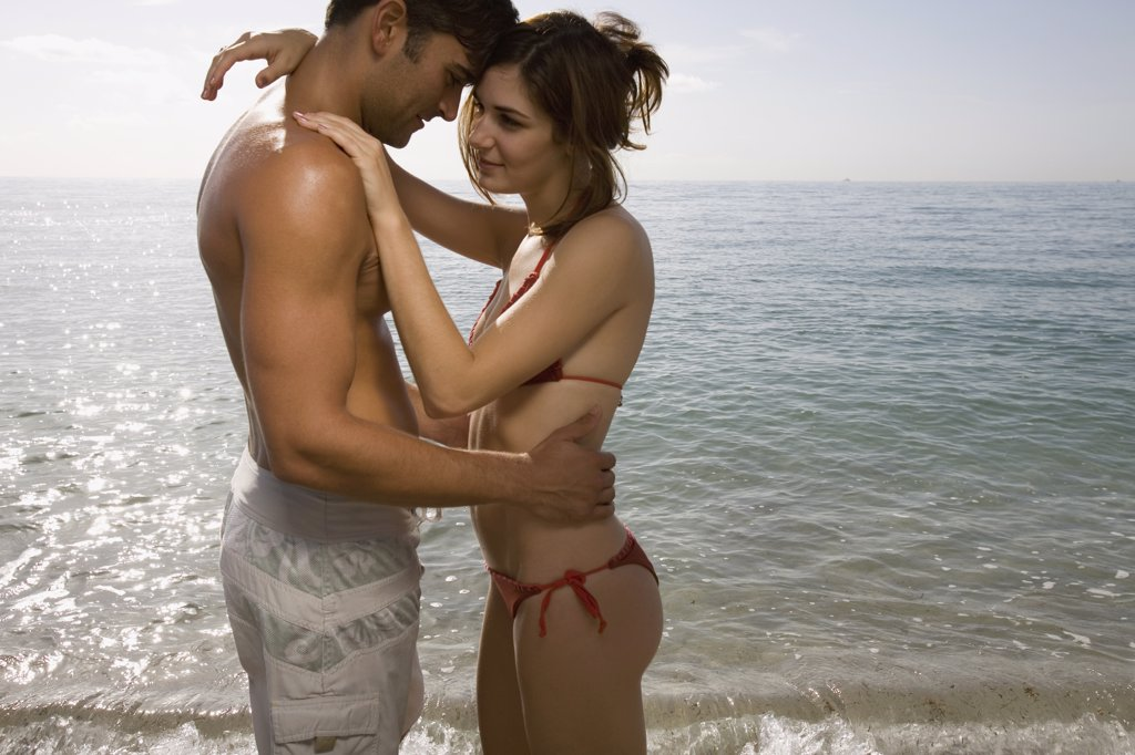 Couple embracing in front of sea : Stock Photo