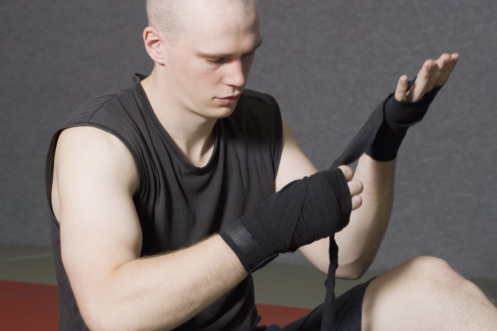 Male boxer wrapping strap around hand : Stock Photo