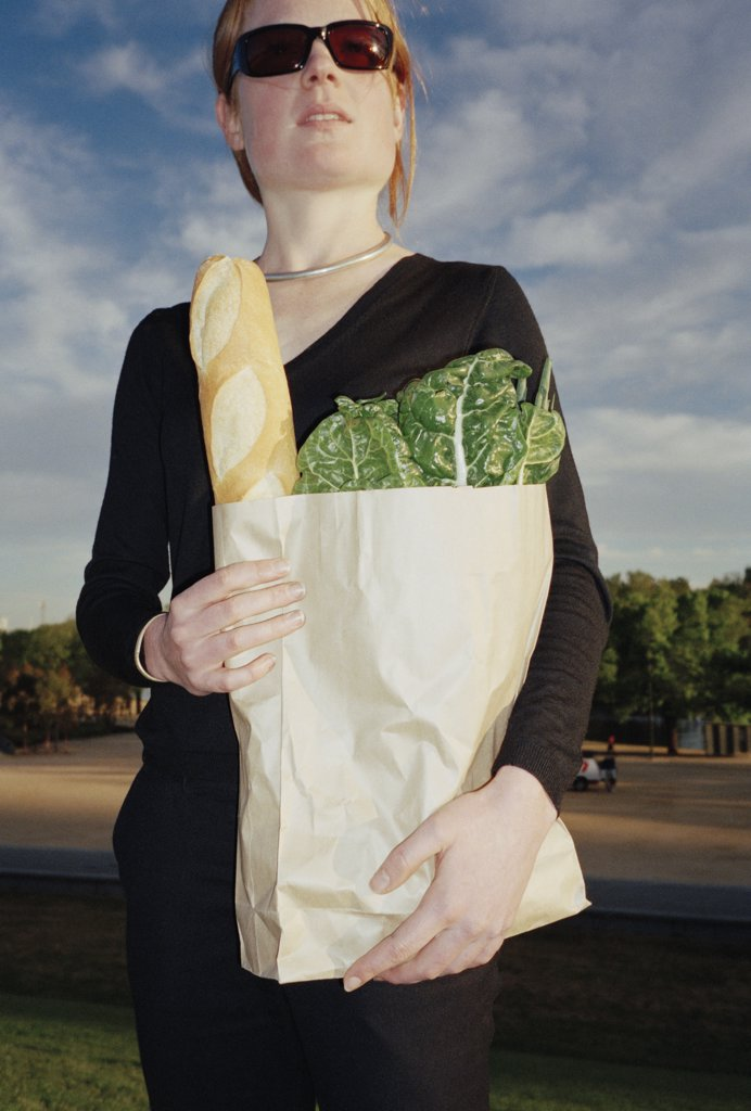 Woman standing in a park and holding a bag of groceries : Stock Photo