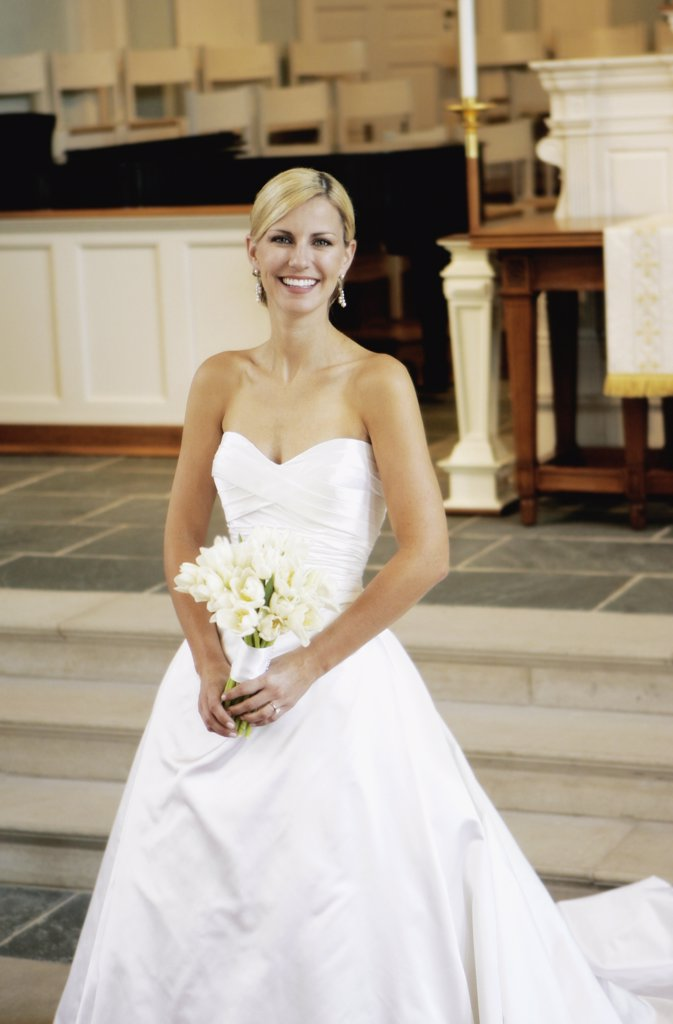 Stock Photo: 1570R-114962 Bride holding wedding bouquet whilst standing at altar