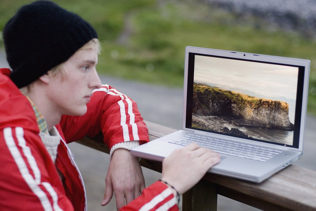 Stock Photo: 1570R-115030 Young man using laptop outdoors