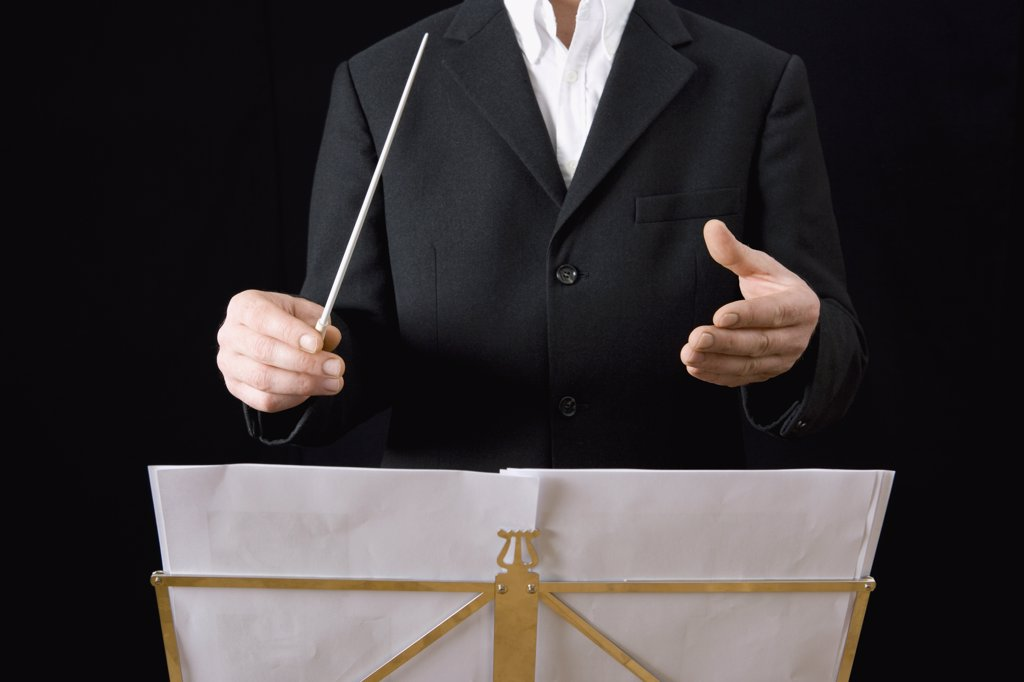 Conductor standing behind stand with sheet music : Stock Photo