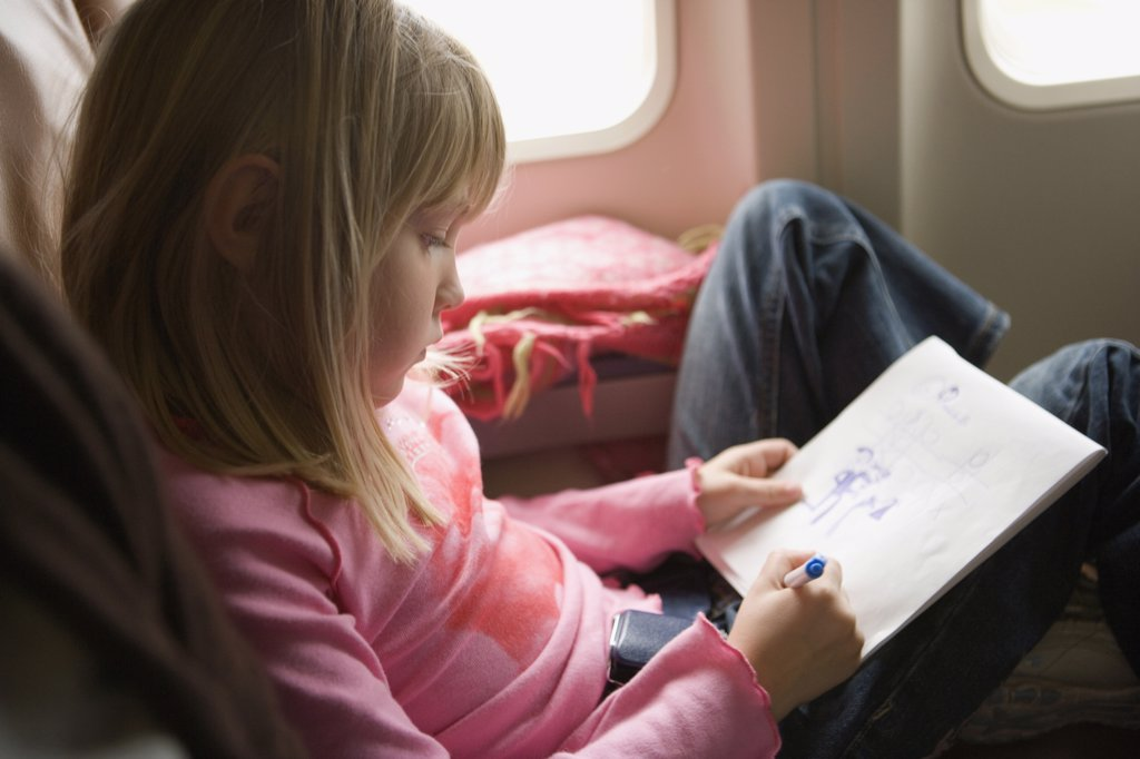 Young girl sitting in an airplane and drawing in a sketch pad : Stock Photo