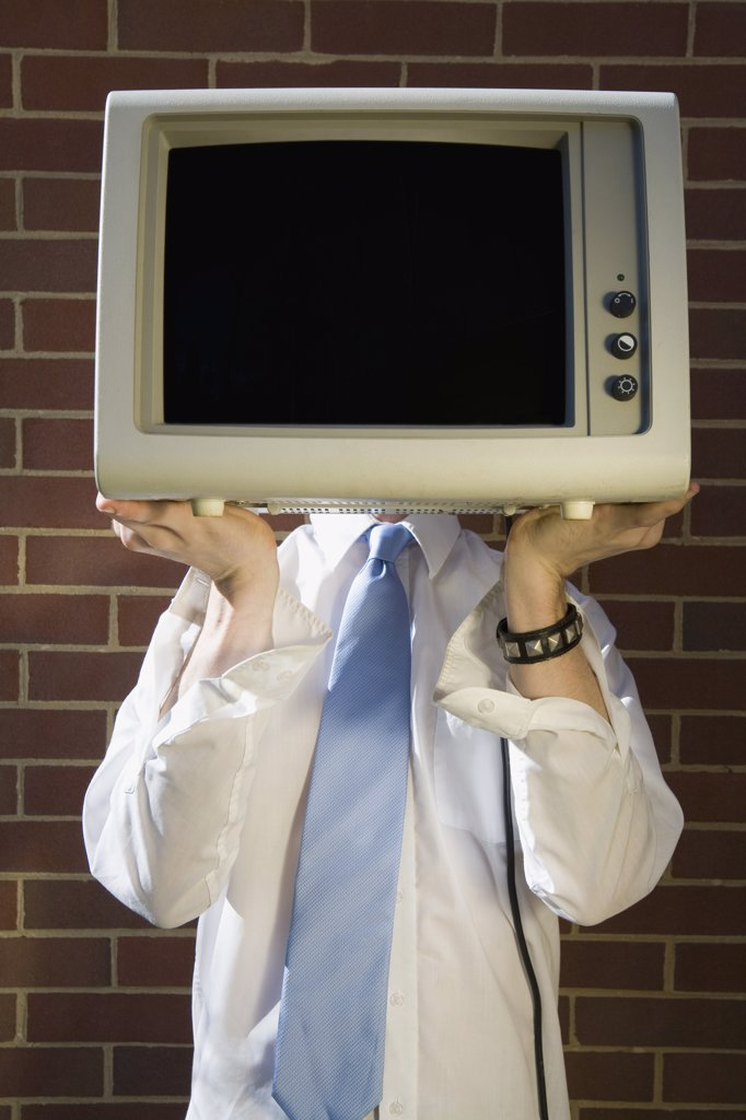 Man holding a television in front of his face : Stock Photo