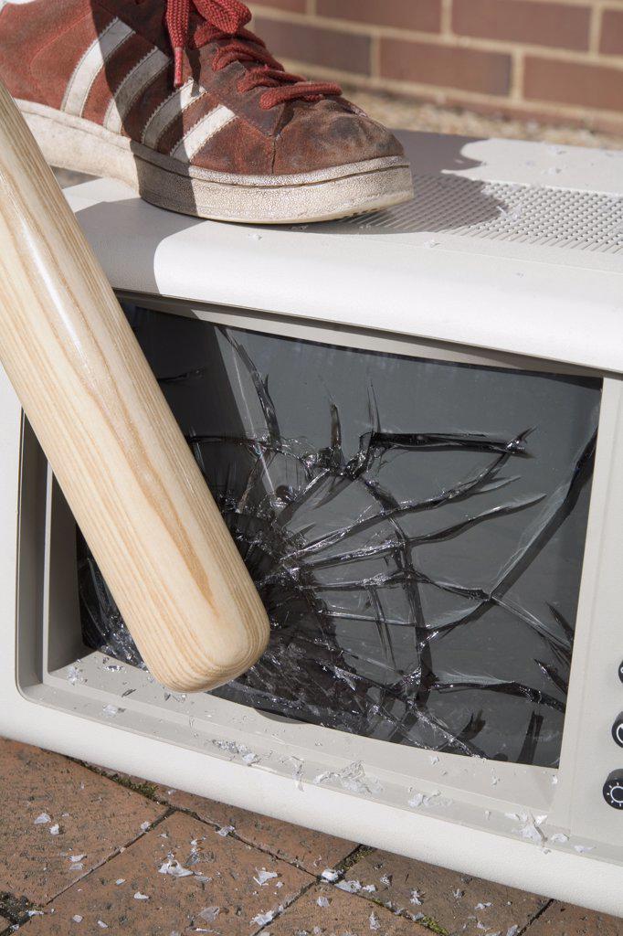 Man holding a baseball bat to a smashed monitor : Stock Photo