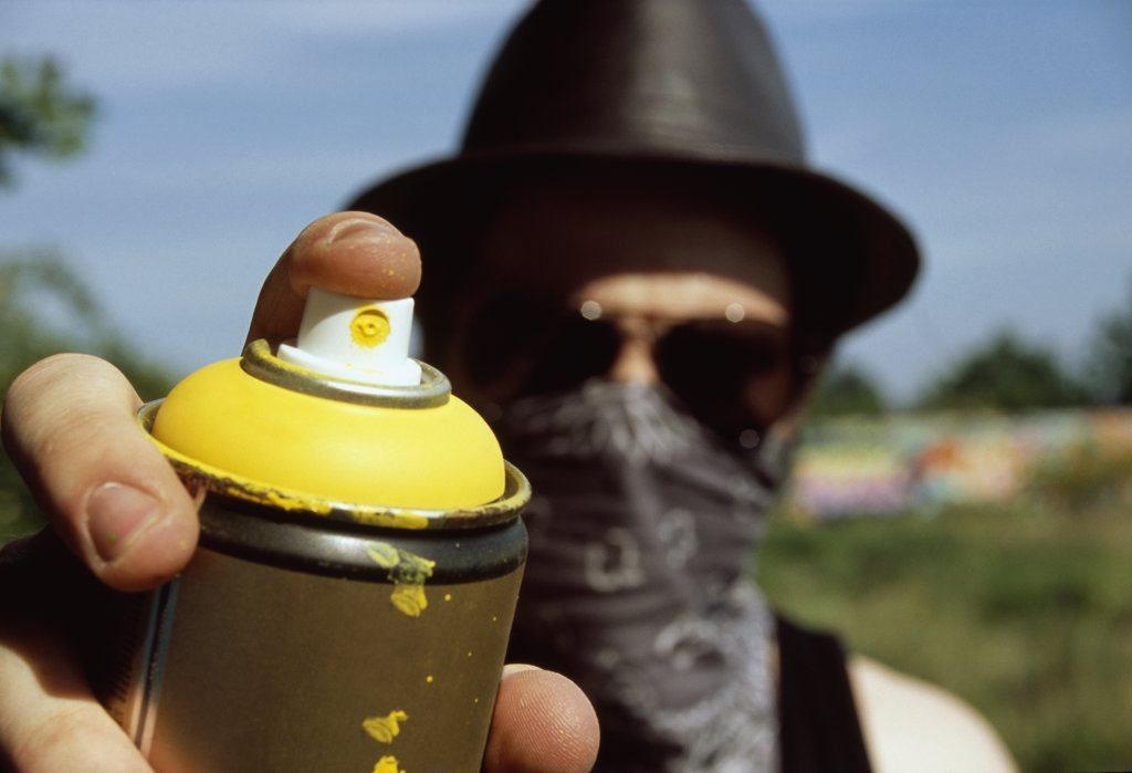 A man holding a can of spray paint : Stock Photo