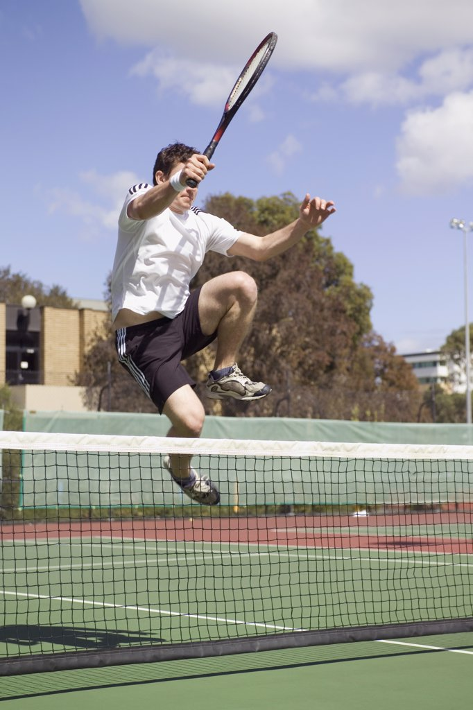 Stock Photo: 1570R-116502 A tennis player leaping over a tennis net