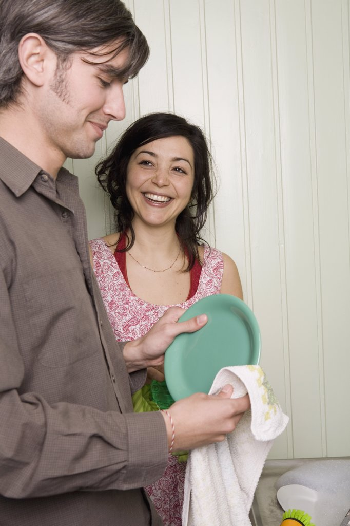 Stock Photo: 1570R-116591 A young couple washing and drying dishes together