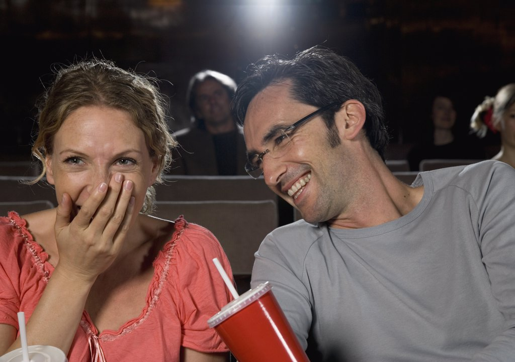 A mid adult couple laughing in a movie theater : Stock Photo