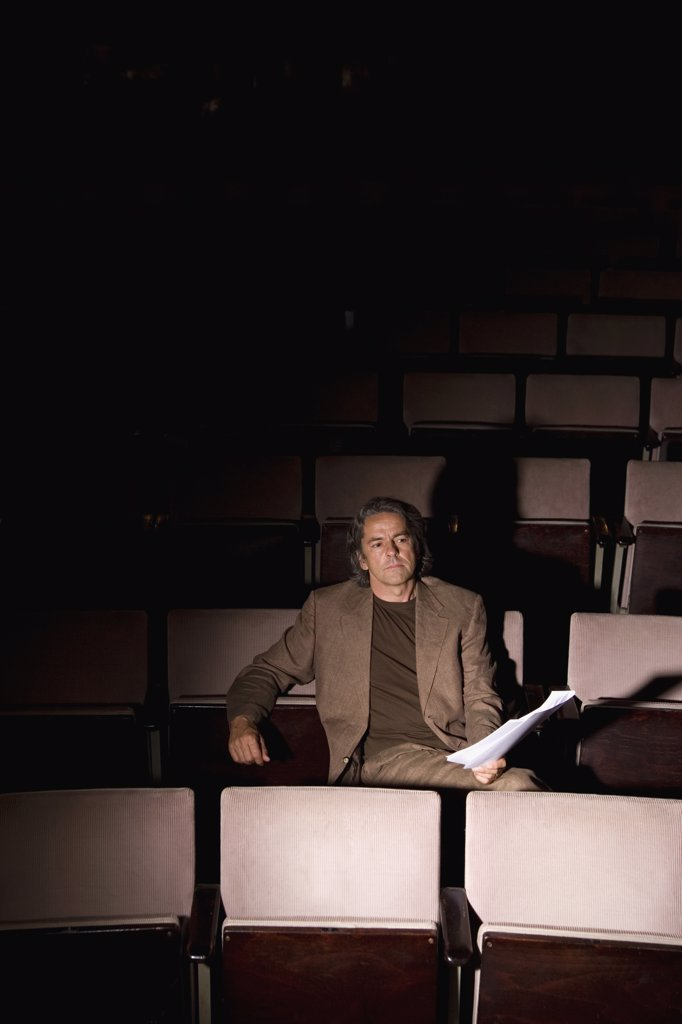 A director sitting in a theater : Stock Photo