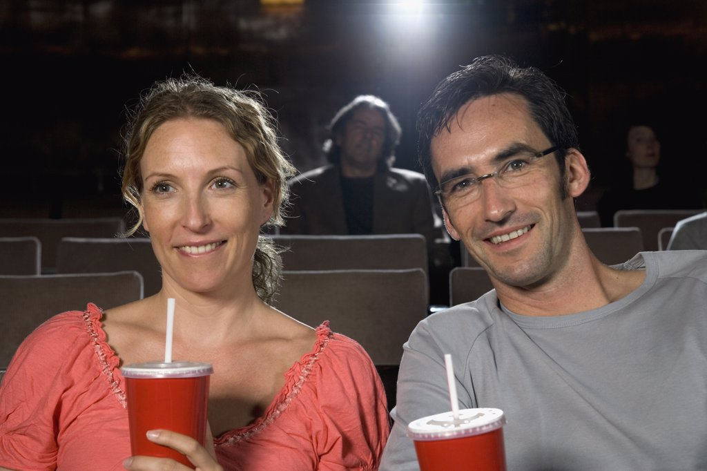 Stock Photo: 1570R-116955 A mid adult couple sitting together in a movie theater