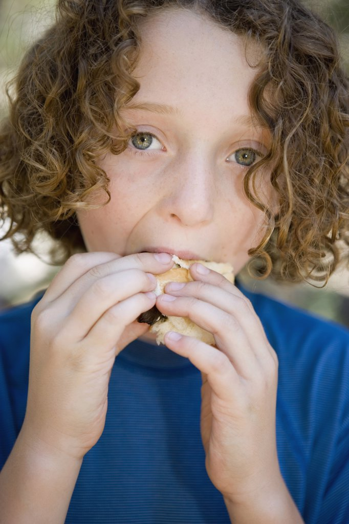 A young boy eating a sausage in a bread roll : Stock Photo