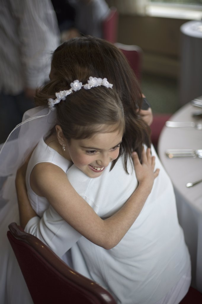 A young girl in her holy communion dress hugging her mother : Stock Photo