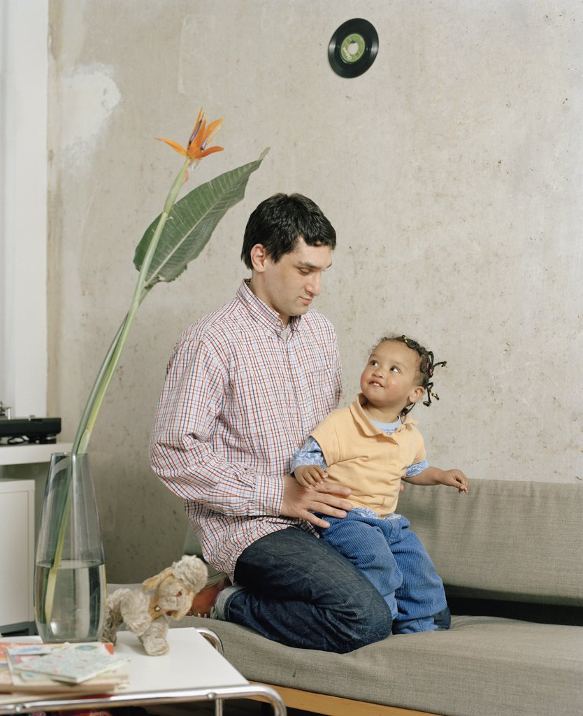 A man kneeling with a toddler on a sofa : Stock Photo