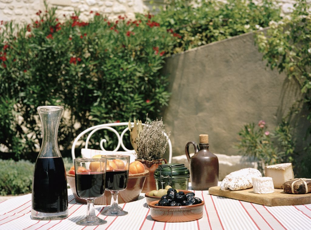An outdoor table set with wine and appetizers : Stock Photo
