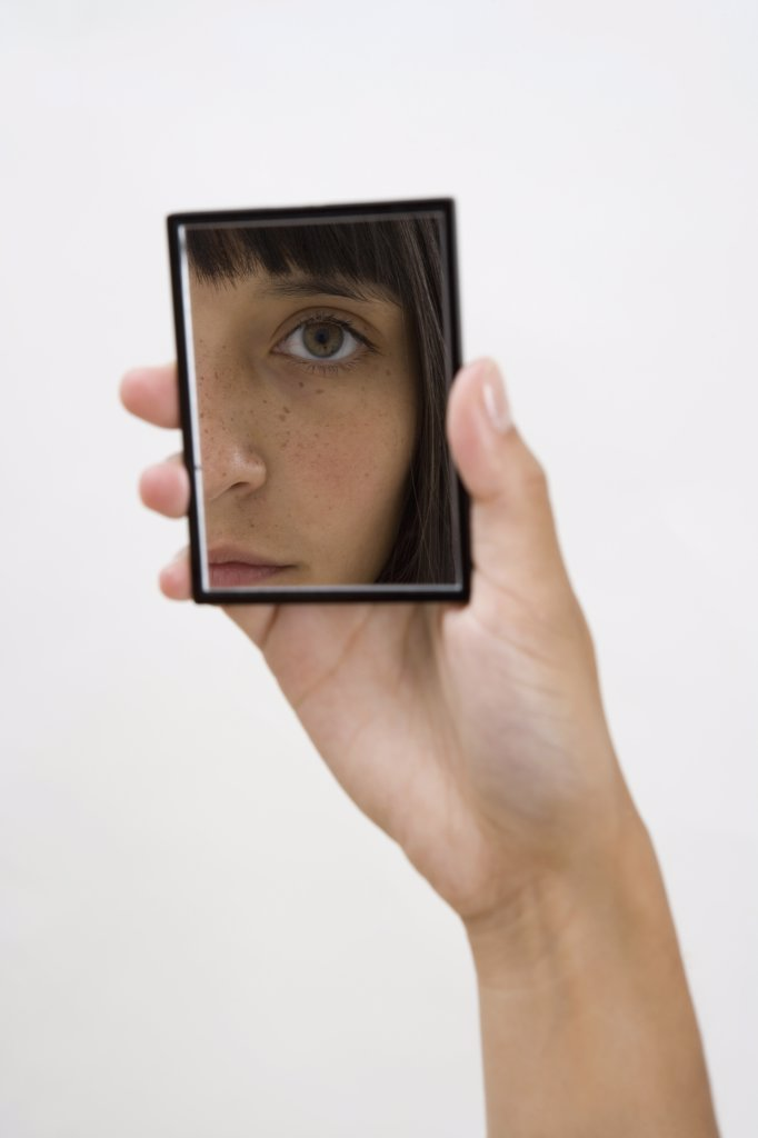 Stock Photo: 1570R-118121 A woman looking into a hand mirror