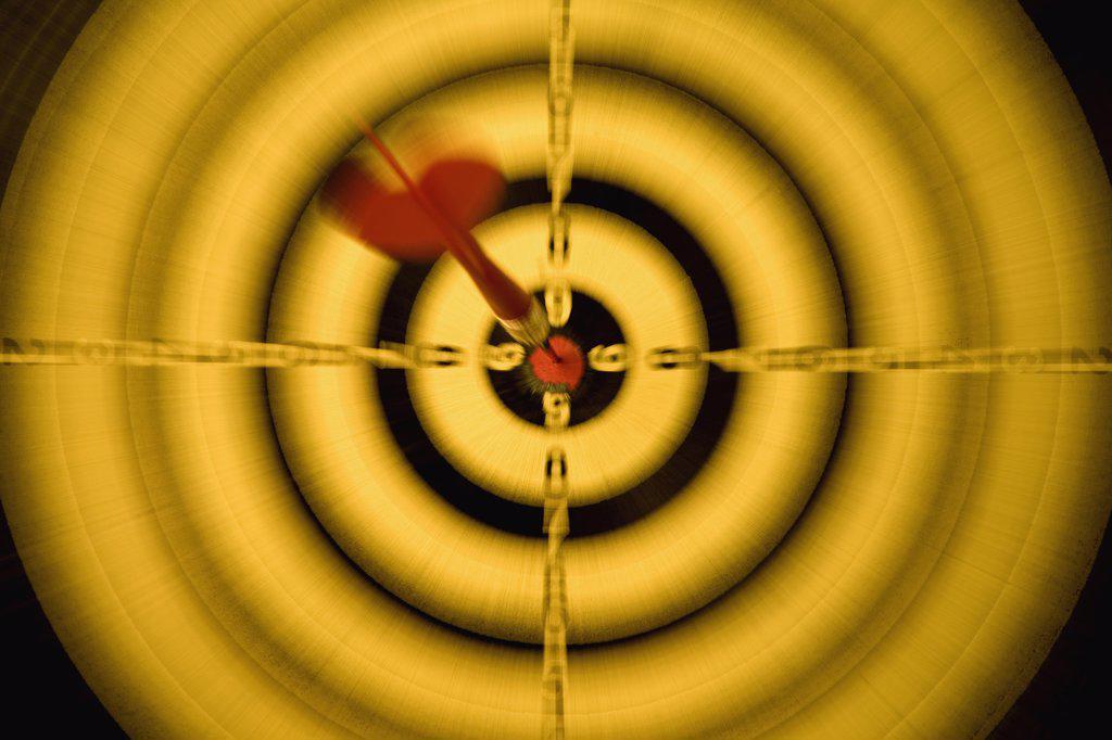 Stock Photo: 1570R-118429 A dart in the bull's eye of a dartboard