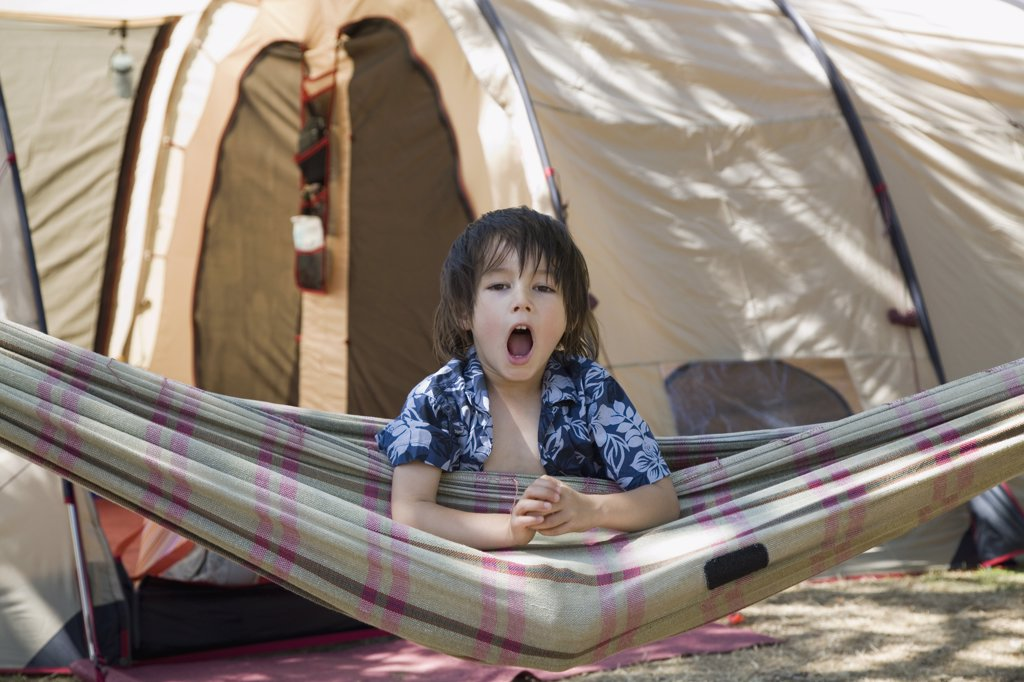 Stock Photo: 1570R-118761 A boy sitting in a hammock and yawning