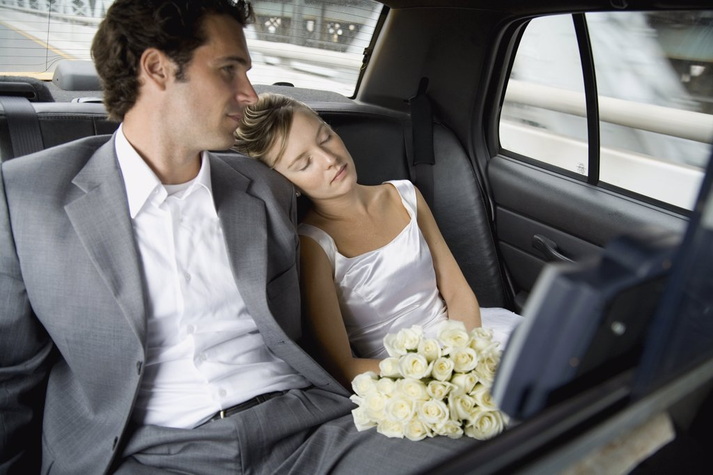 A bride and groom relaxing in a car : Stock Photo