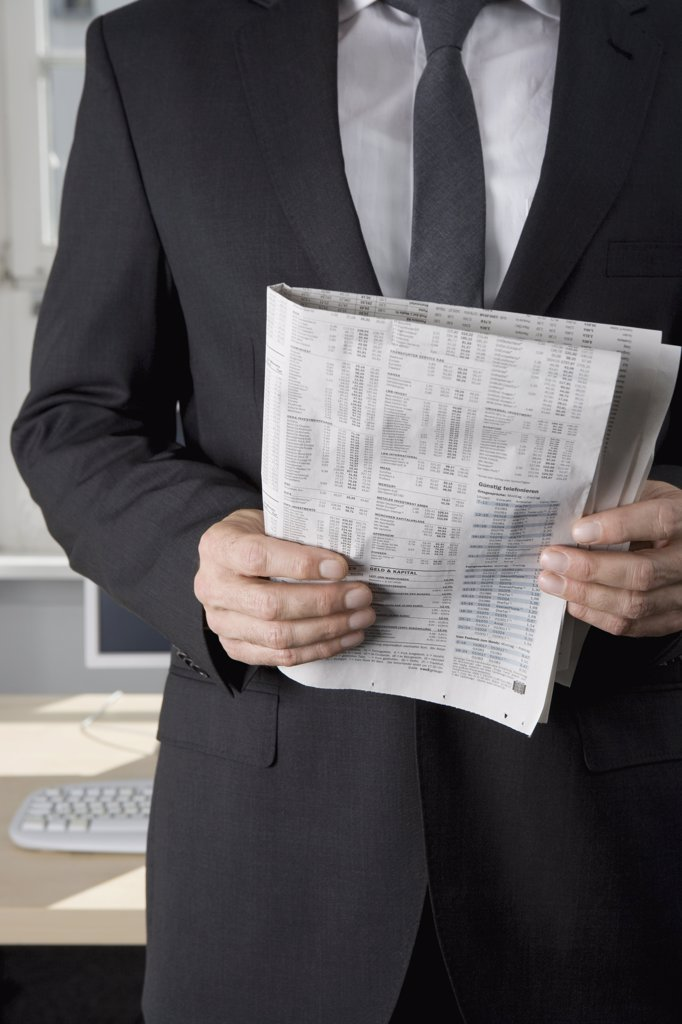 A businessman holding a newspaper : Stock Photo