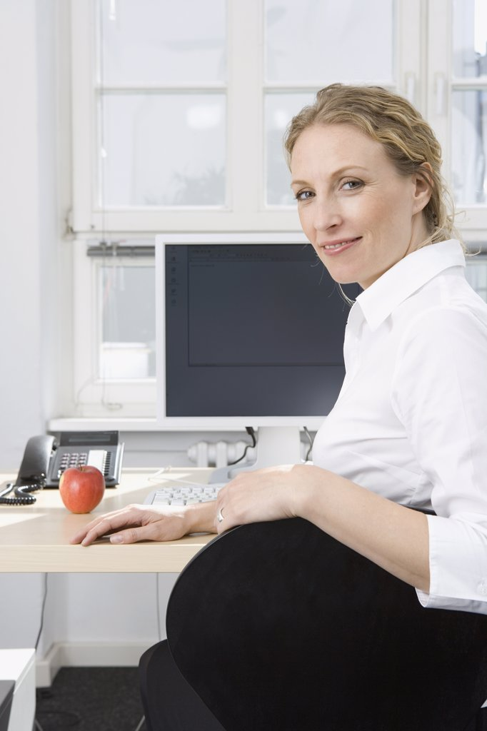 Stock Photo: 1570R-118876 A businesswoman sitting at a desk