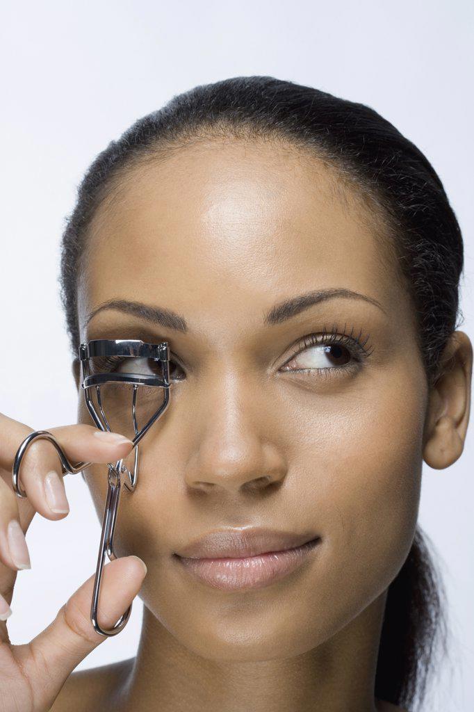 A woman using an eyelash curler : Stock Photo