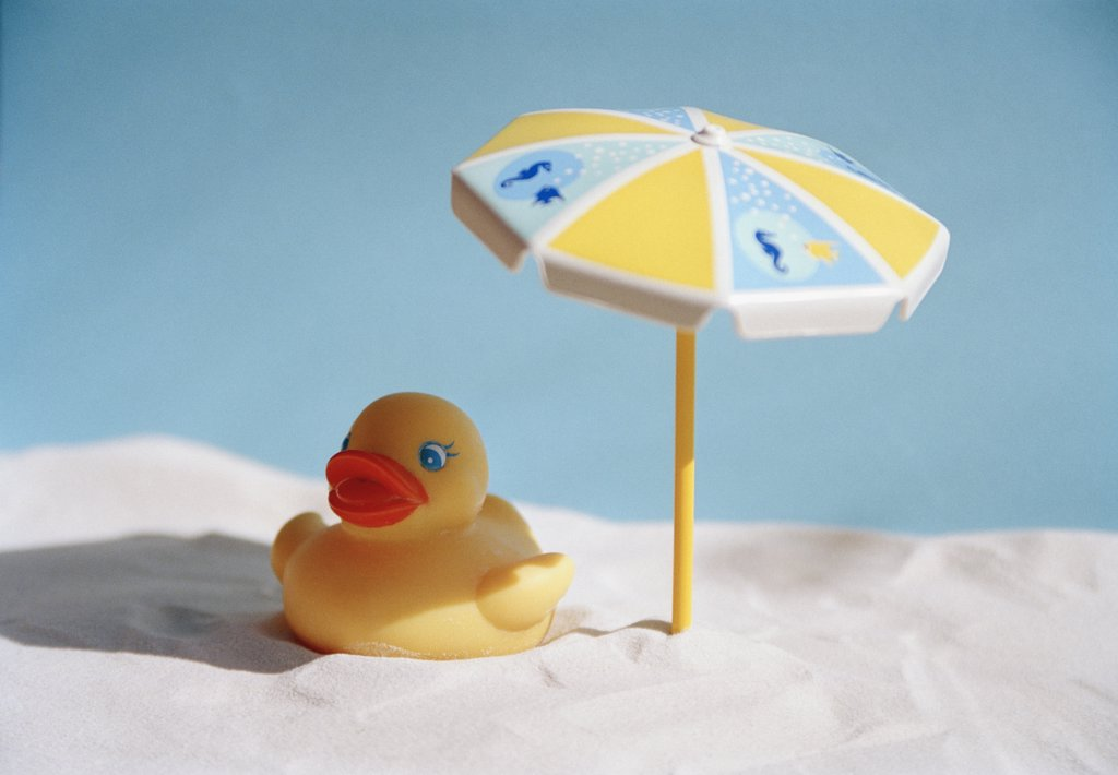Stock Photo: 1570R-119128 A toy duck and parasol on the beach