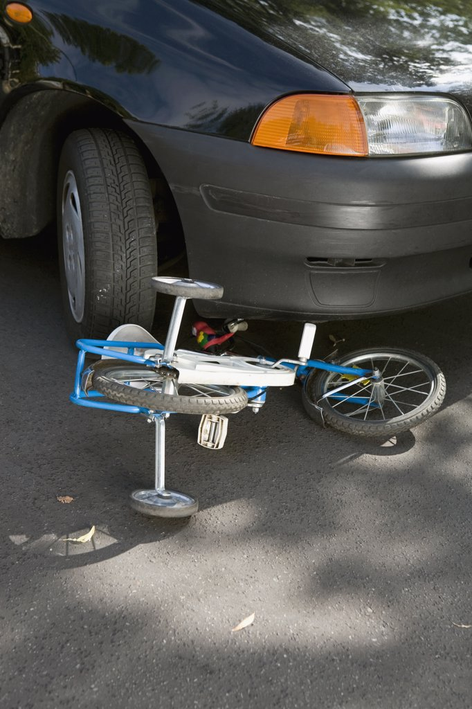 Stock Photo: 1570R-119223 A child's bicycle lying on the road underneath a car