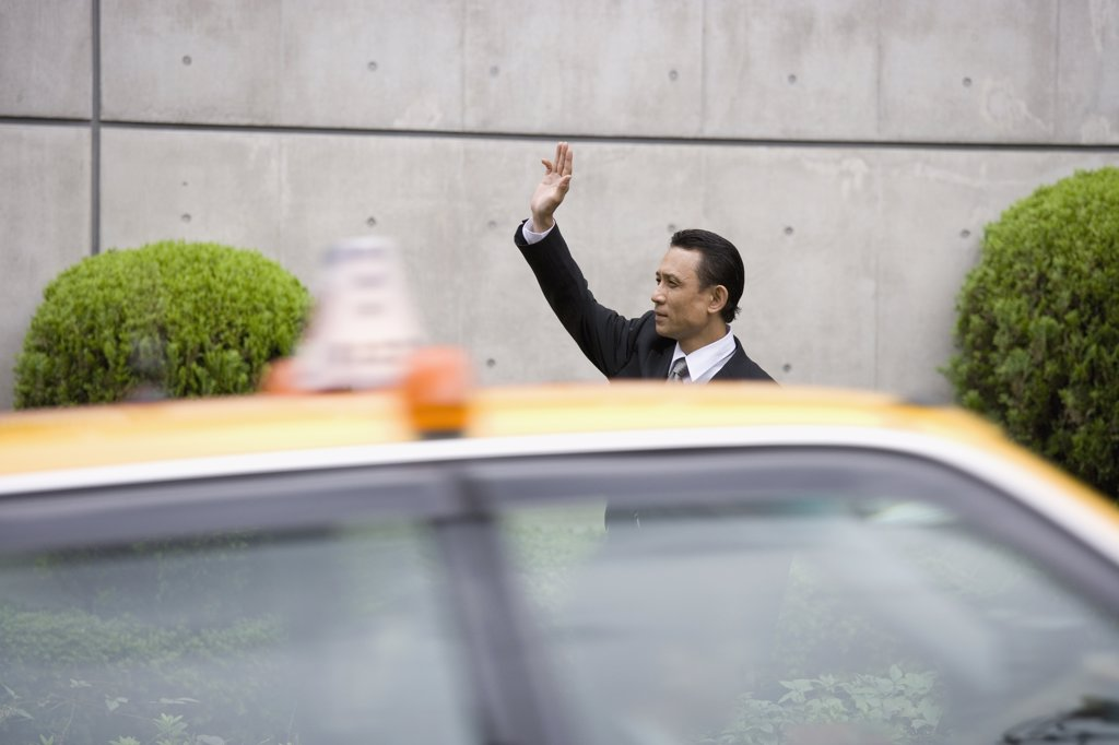 A businessman hailing a taxi : Stock Photo