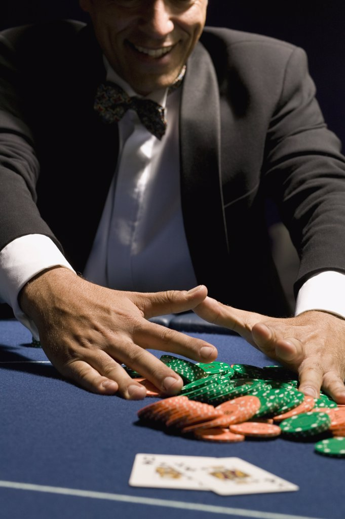 Stock Photo: 1570R-119364 Man gathering his chips after a gambling win