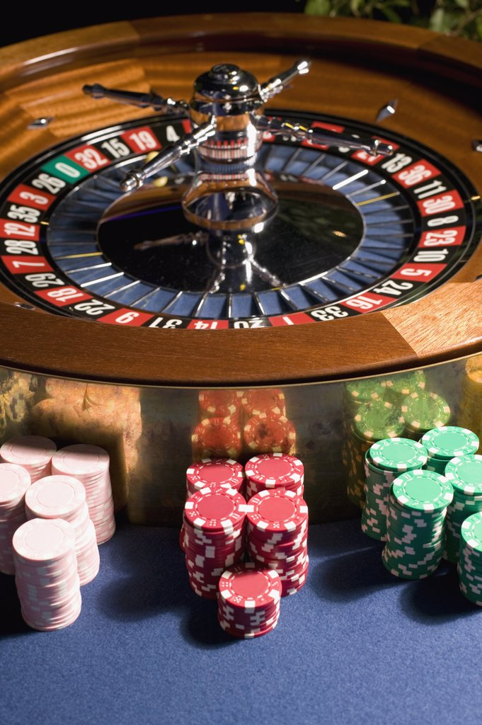 Roulette wheel with stacks of gambling chips : Stock Photo