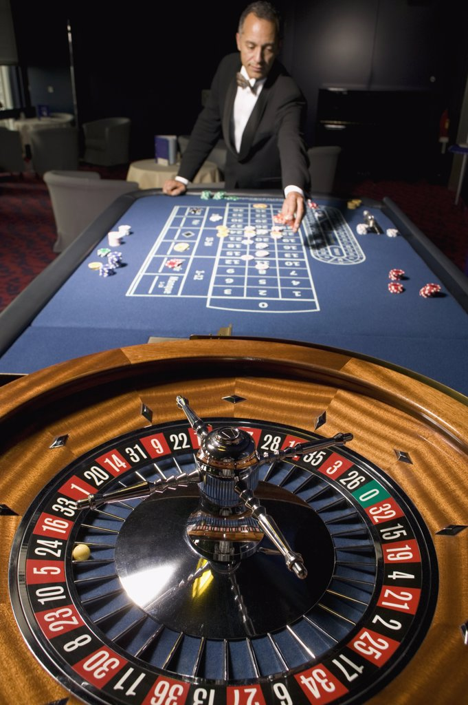 Stock Photo: 1570R-119380 Man placing a bet at the Roulette table