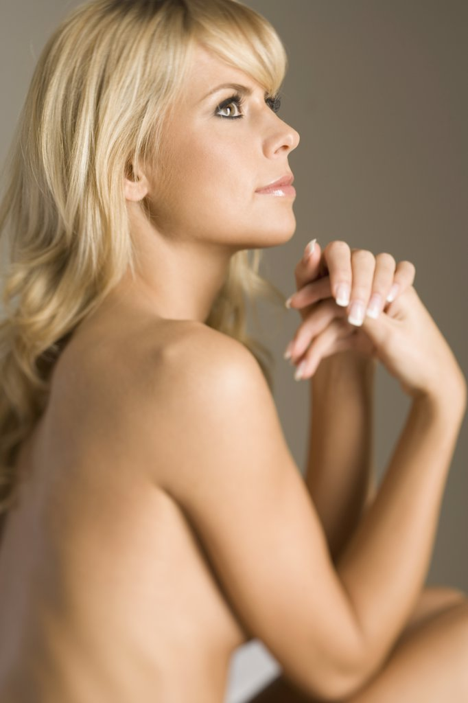 Stock Photo: 1570R-119983 Naked woman sitting with hands clasped near chin