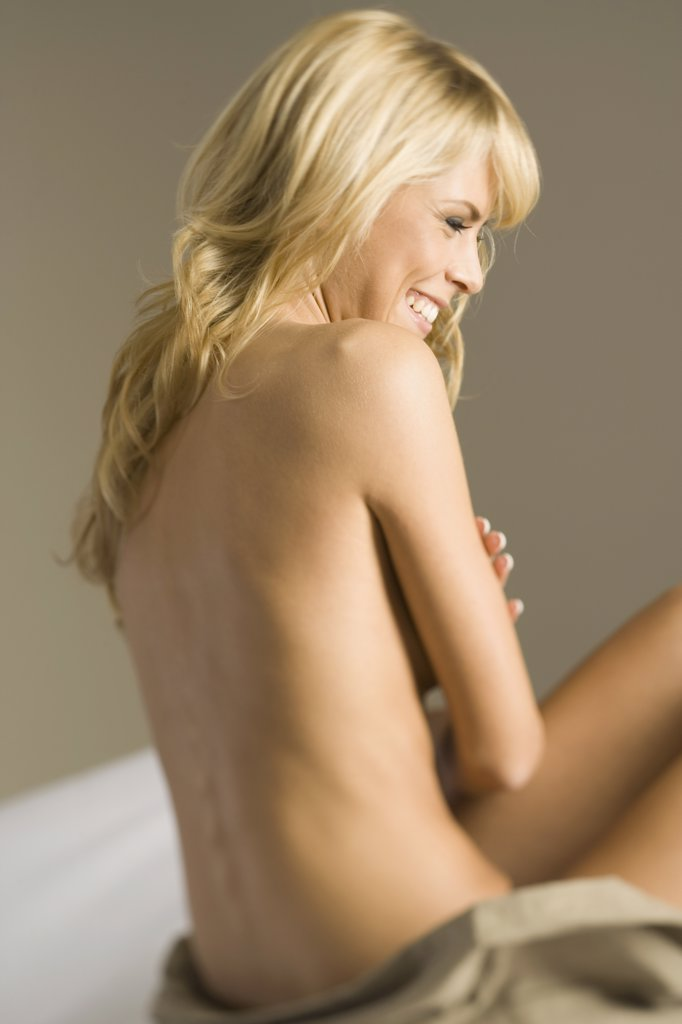 Naked woman sitting on a bed with her arms crossed : Stock Photo