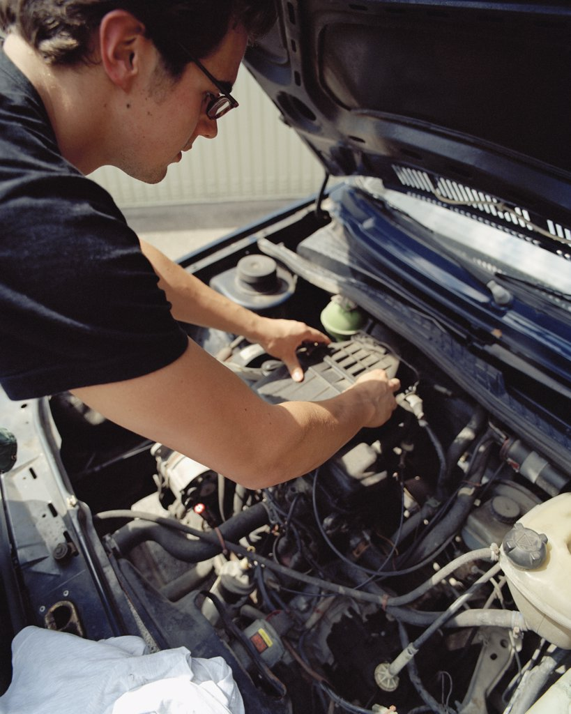 Young man checking a car battery : Stock Photo