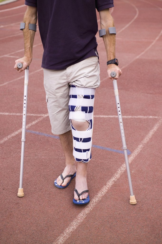 Stock Photo: 1570R-120230 Man with his leg in a brace and using crutches