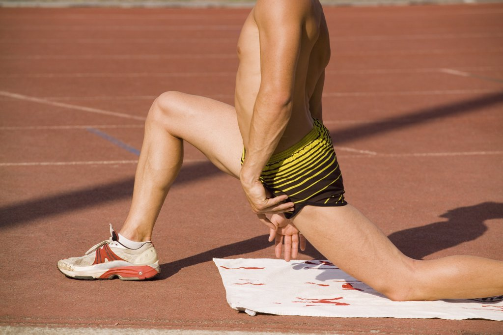 Stock Photo: 1570R-120274 Male athlete stretching on the edge of a running track