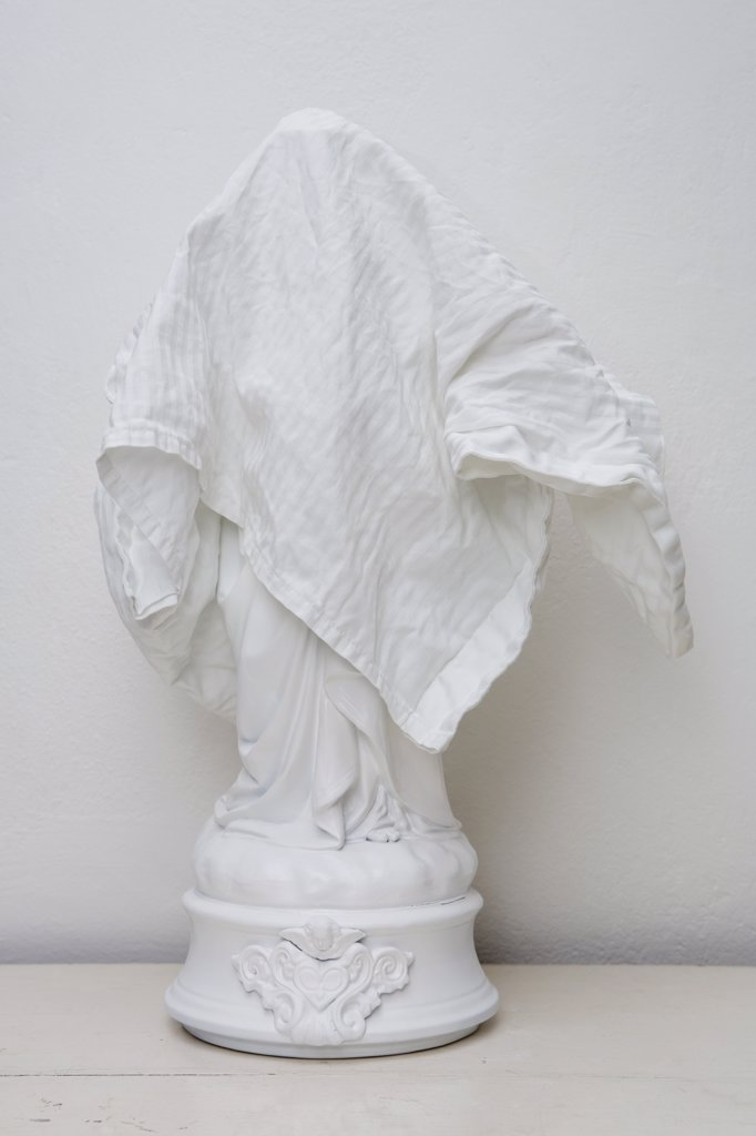 White figurine covered by white cloth : Stock Photo