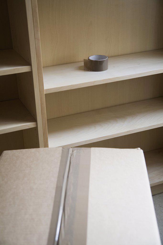 Stock Photo: 1570R-120433 Packing box next to an empty bookshelf