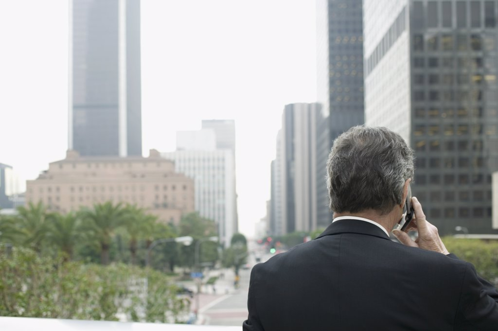 Businessman using a mobile phone on a balcony in the financial district : Stock Photo